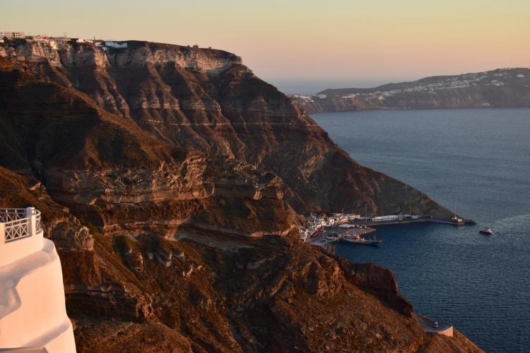 A golden sun sets over volcanic cliffs as seen from the Volcano View Hotel in Santorini Greece