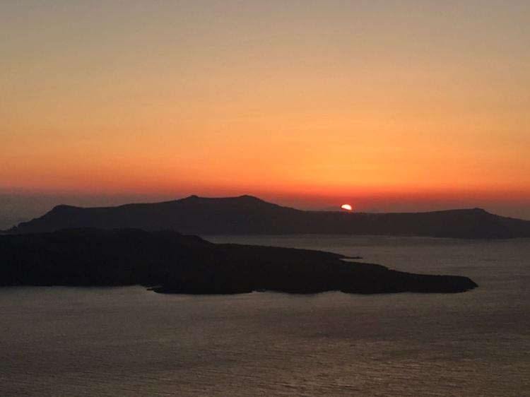 The sun sets behind the caldera in Santorini Greece