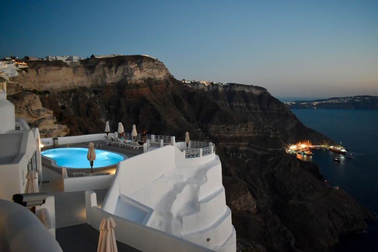 A view of one of the pools at Volcano View Hotel at sunset in Santorini Greece