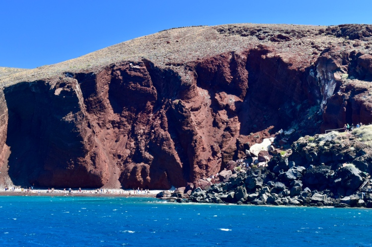 A view of the red beach from the water in Santorini Greece
