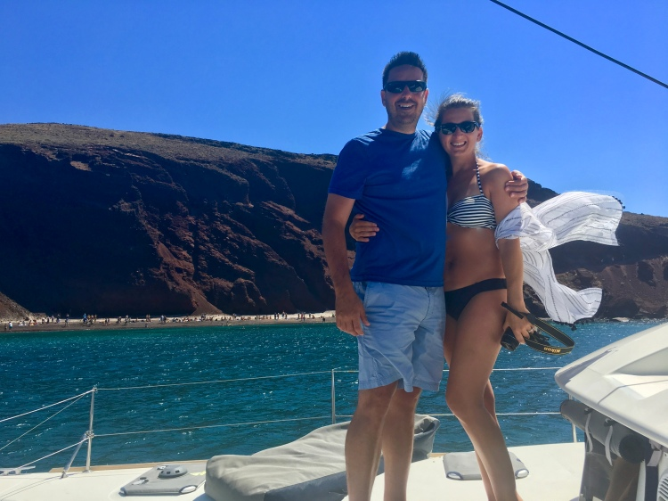 Erin from Cathedrals and Cafes blog poses with her husband in front of red beach on the catamaran Tonina in Santorini Greece