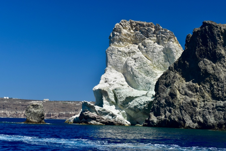 A large limestone rock formation as seen from the water in Santorini Greece