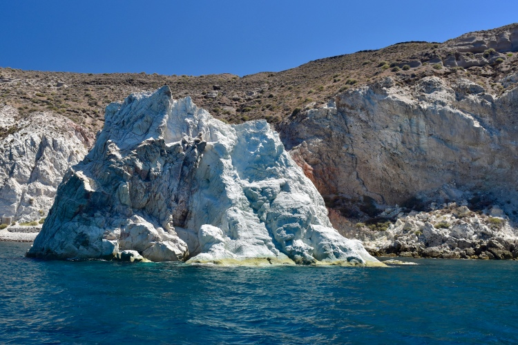 A large limestone rock formation and beginning of white beach in Santorini Greece