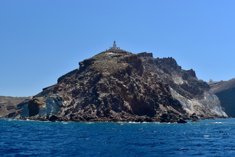 A lighthouse stands atop a steep cliff in Santorini Greece