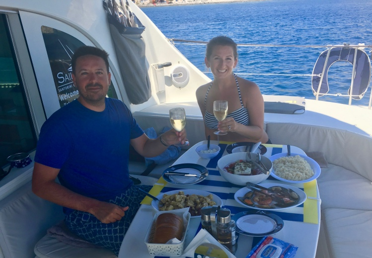 Erin from Cathedrals and Cafes blog and her husband enjoy a lunch of seafood and chicken on catamaran Tonina in Santorini Greece