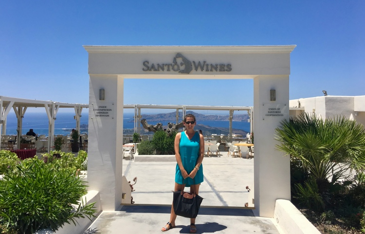 Erin from Cathedrals and Cafes blog stands at the entrance to Santo Wines Winery in Santorini Greece
