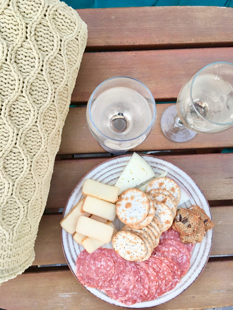 A plate of charcuterie with two glasses of white wine and a knitted blanket