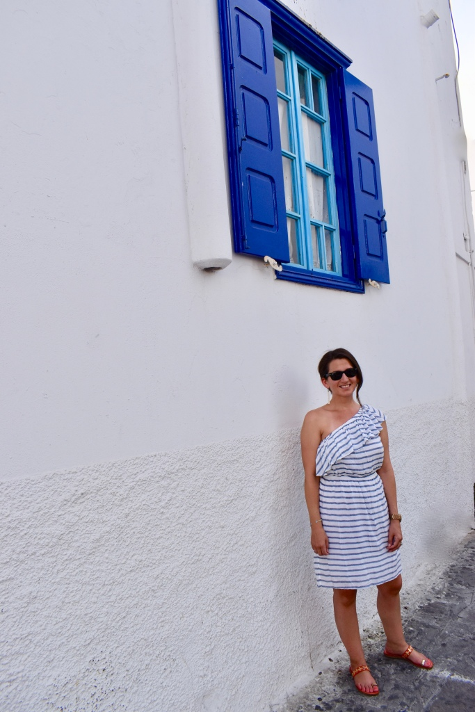 Erin from Cathedrals and Cafes blog poses below blue window shutters in Mykonos Greece