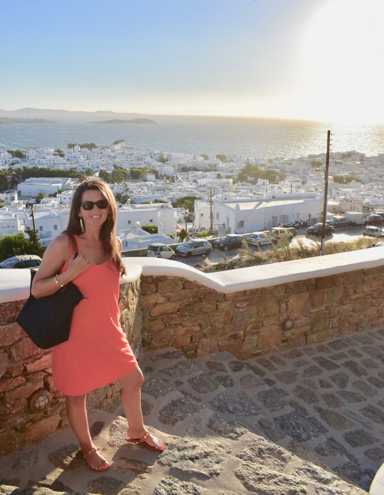 Erin from Cathedrals and Cafes Blog poses on a stone stairway walking down to Mykonos Town in Greece