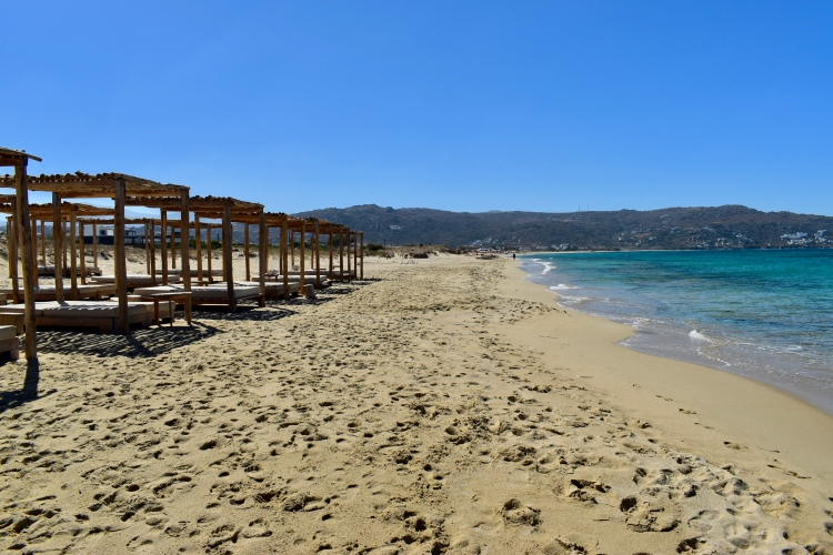 A row of wooden lounge beds sit empty on a Naxos beach in Greece