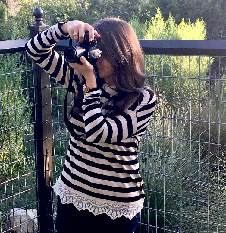 Erin from Cathedrals and Cafes blog wears a black and cream striped long sleeve t-shirt and takes photos with a Nikon D5500 DSLR camera