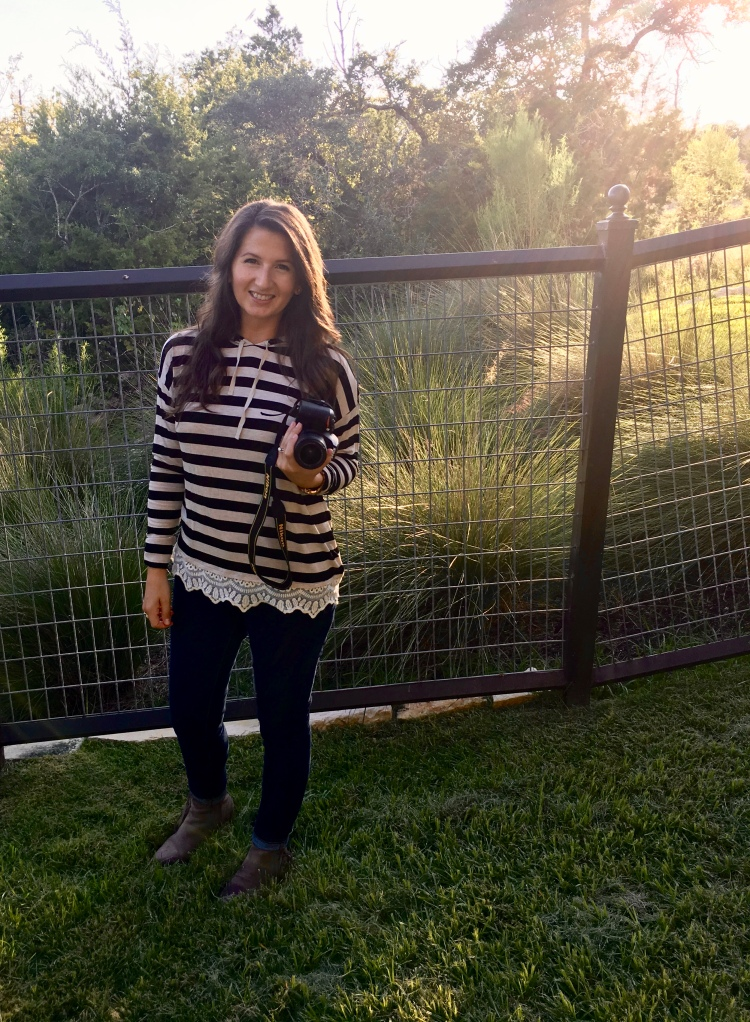 Erin from Cathedrals and Cafes blog poses in her backyard with the sun setting behind her.