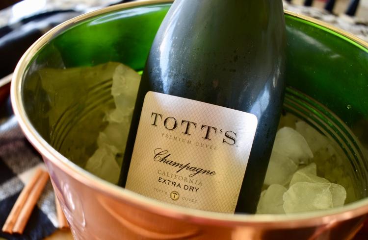A bottle of Tott's champagne in a copper ice bucket