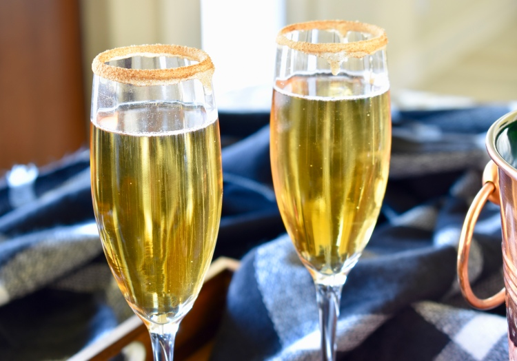 Two champagne flutes filled with apple cider mimosas