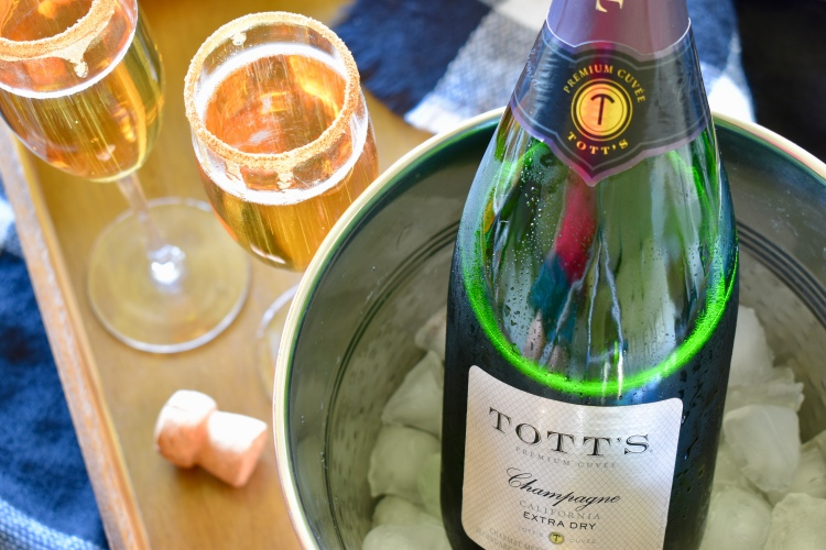 A tray of Tott's champagne in a copper ice bucket with two glasses of apple cider mimosas