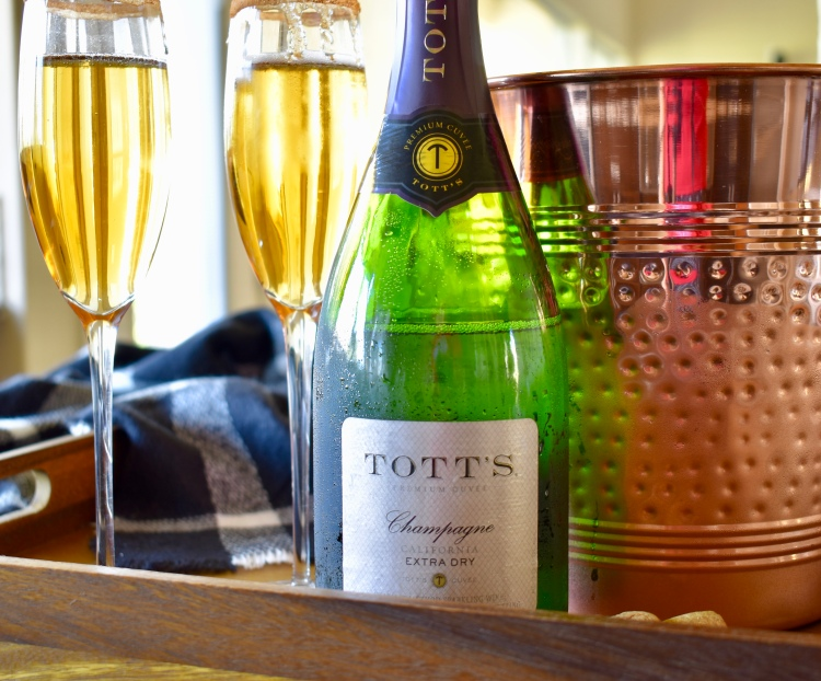 A tray of mimosas holds a copper ice bucket, a bottle of Tott's champagne and two flutes of apple cider mimosas