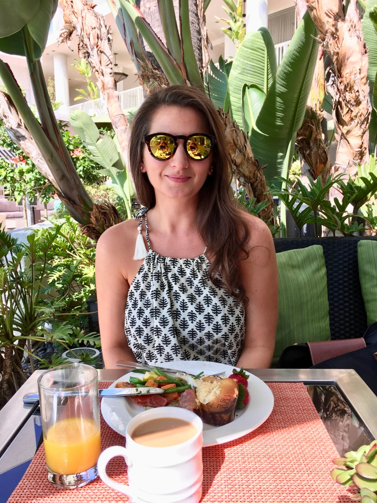 Erin from Cathedrals and Cafes blog sits poolside having breakfast at the Beverly Hilton Hotel in Los Angeles California