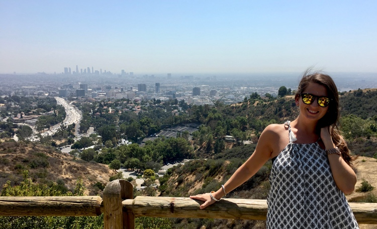 Erin from Cathedrals and Cafes blog poses against the railing overlooking Los Angeles at the Mulholland Drive scenic overlook