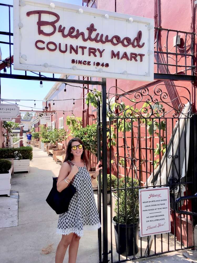 Erin from Cathedrals and Cafes blog poses at the entrance gate to Brentwood Country Mart