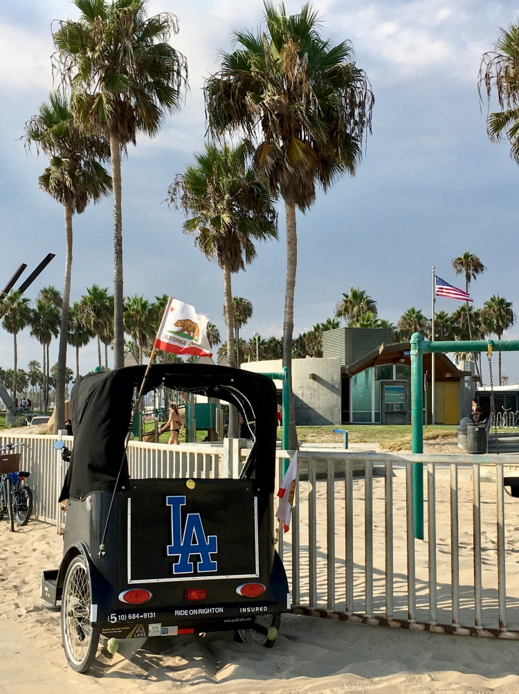 A pedicab with LA and California insignia on Venice Beach